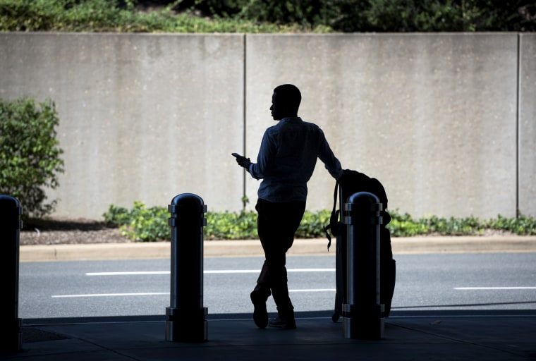 Image: A man waits for a ride-hailing service at Ronald Reagan Washington National Airport on Aug. 24, 2016.