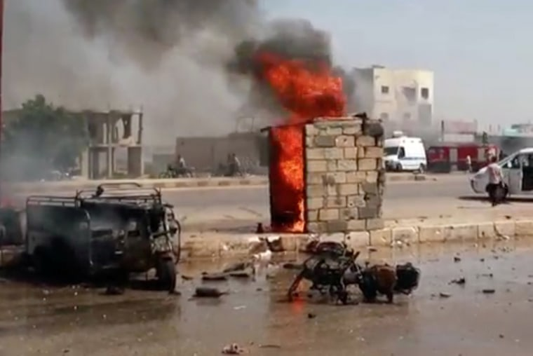 Image: A burnt out car and a motorbike on a road in a town, said to be Saraqib, Idlib province, Syria