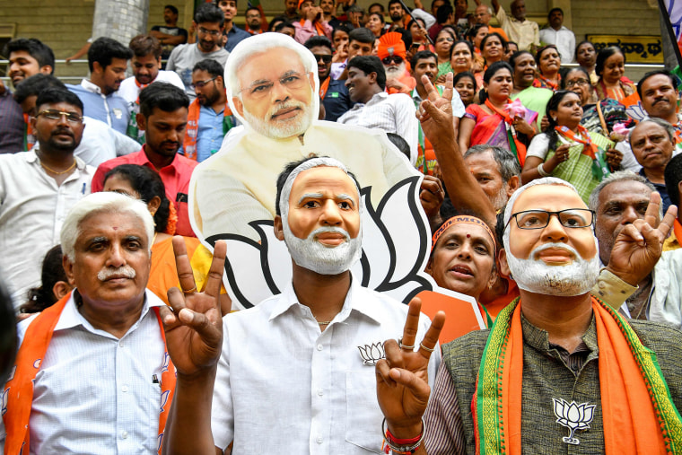 Image: Indian supporters and party workers of Bharatiya Janata Party (BJP) wear masks of Indian Prime Minister Narendra Modi and flash victory signs as they celebrate on the vote results day for India's general election in Bangalore