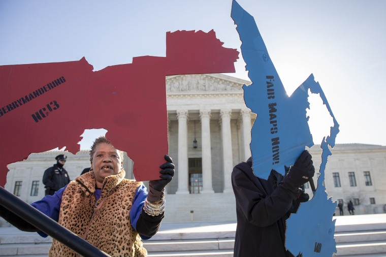 Activists at the Supreme Court opposed to partisan gerrymandering hold up representations of congressional districts from North Carolina, left, and Maryland, right, as justices hear arguments about the practice of political parties manipulating the boundary of a congressional district to unfairly benefit one party over another on  March 26, 2019.
