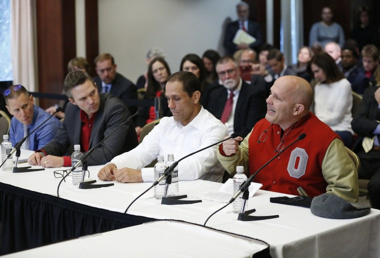 Michael DiSabato, right, speaks with other victims of former Ohio State team doctor Dr. Richard Strauss, at the university's board of trustees meeting on Nov. 16, 2018 in Columbus.