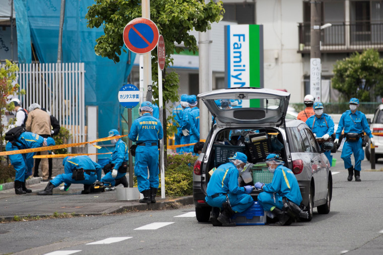 Image: Police forensic experts work at the crime scene where a man stabbed 19 people, including children in Kawasaki