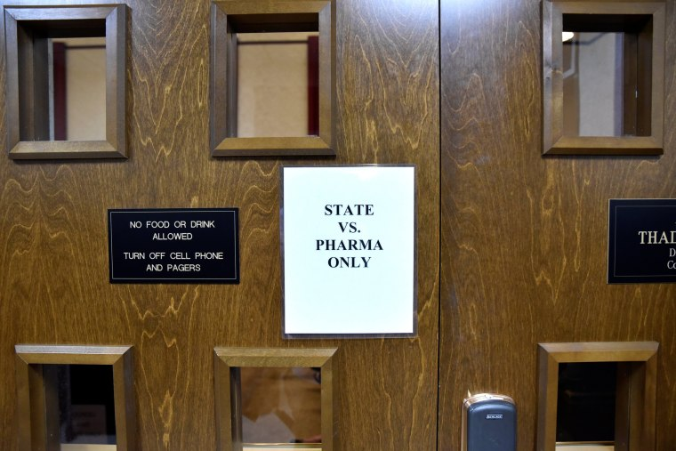 Image: A sign is seen on the outside of the courtroom on the first day of a trial of Johnson & Johnson and Teva Pharmaceutical Industries in Norman