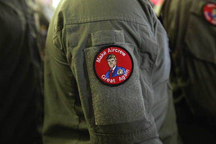 "Image: A service member wears a patch that says ""Make Aircrew Great Again"" as they listen to President Donald Trump speak to troops at a Memorial Day event aboard the USS Wasp"