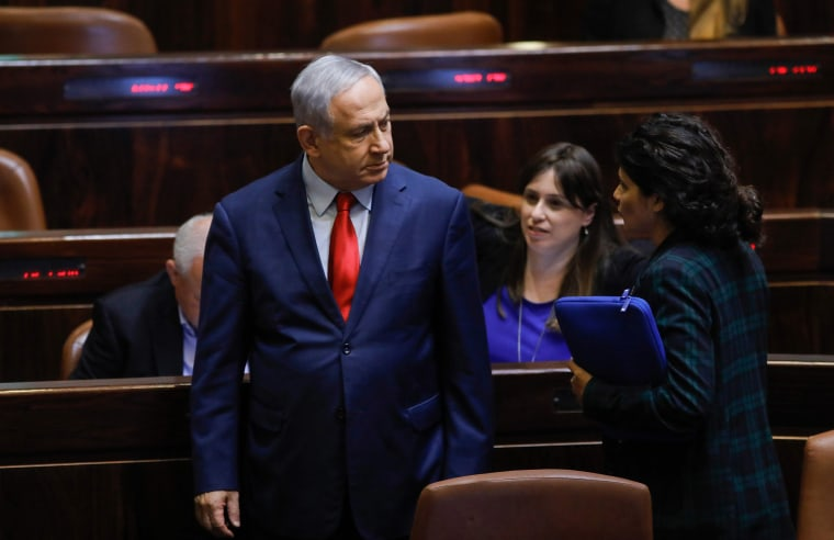 Image: Israeli Prime Minister Benjamin Netanyahu stands during a vote on a bill to dissolve the Knesset