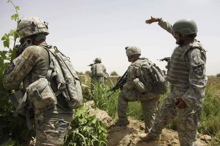 An Afghan interpreter, right, on patrol with 2nd Platoon, Alpha Company, 2nd Battalion, 1st Infantry Regiment of the 5th Stryker Brigade, calls over some local teenagers who were seen moving suspiciously in a tree line on May 8, 2010, in Afghanistan's Kandahar Province.