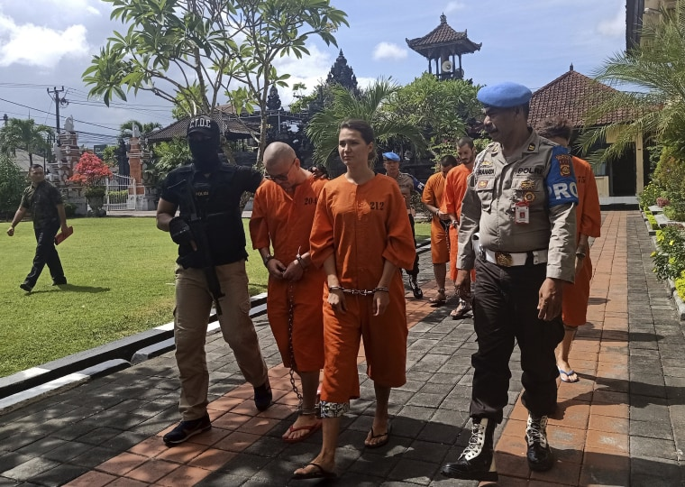 Image: Police officers escort foreign nationals arrested for selling drugs prior to a press conference at the regional police headquarters in Denpasar, Bali