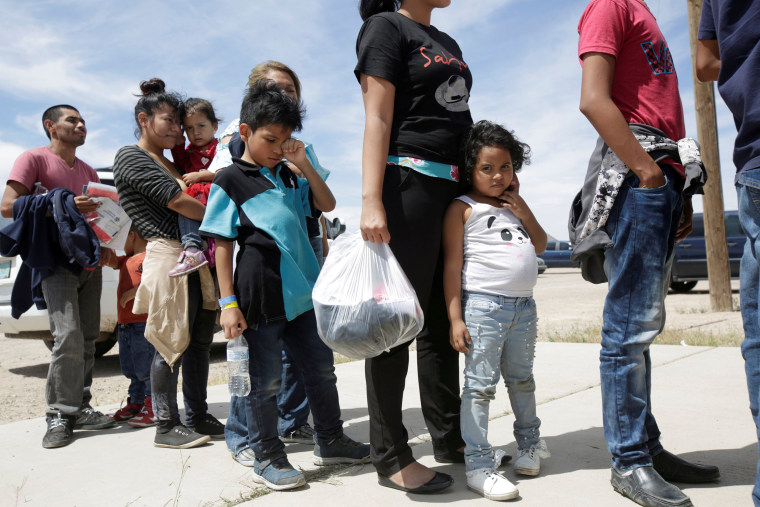 Image: Central American migrants stand in line before entering a temporary shelter, after illegally crossing the border between Mexico and the U.S., in Deming, New Mexico