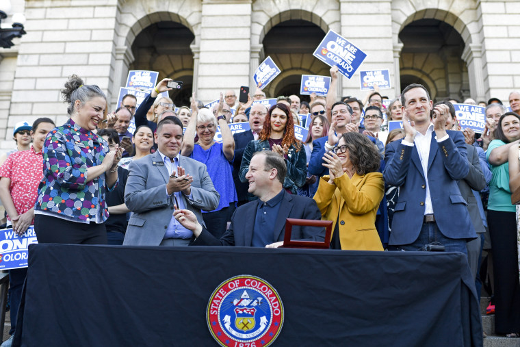 Gov. Jared Polis is applauded upon signing two LGBTQ bills on May 31, 2019.