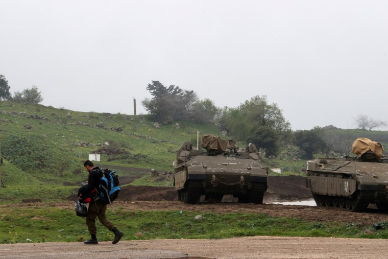 Image: FILE PHOTO: An Israeli soldier walks past armoured Israeli military vehicles in the Israeli-occupied Golan Heights