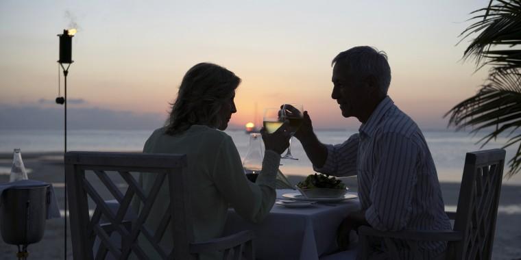 Man sitting on terrace, woman leaning on doorway, smiling, portrait