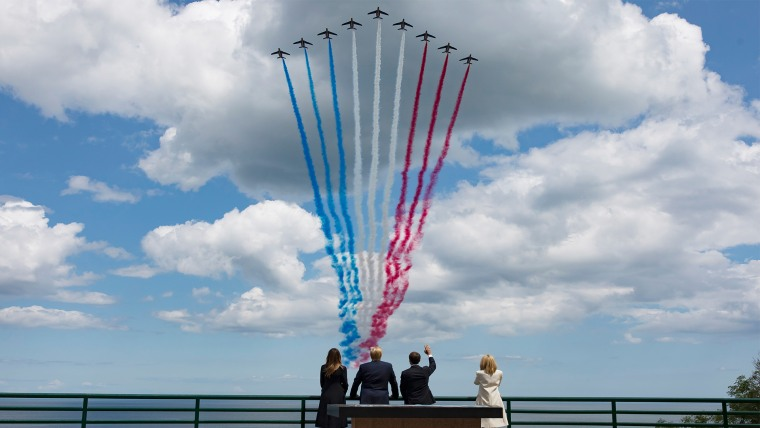 U.S President Donald Trump, U.S First Lady Melania Trump, left, French President Emmanuel Macron, second right, and his wife Brigitte Macron, right, watch jet planes approaching during a ceremony to mark the 75th anniversary of D-Day at the Normandy American Cemetery in Colleville-sur-Mer, Normandy, France, Thursday, June 6, 2019. World leaders are gathered Thursday in France to mark the 75th anniversary of the D-Day landings