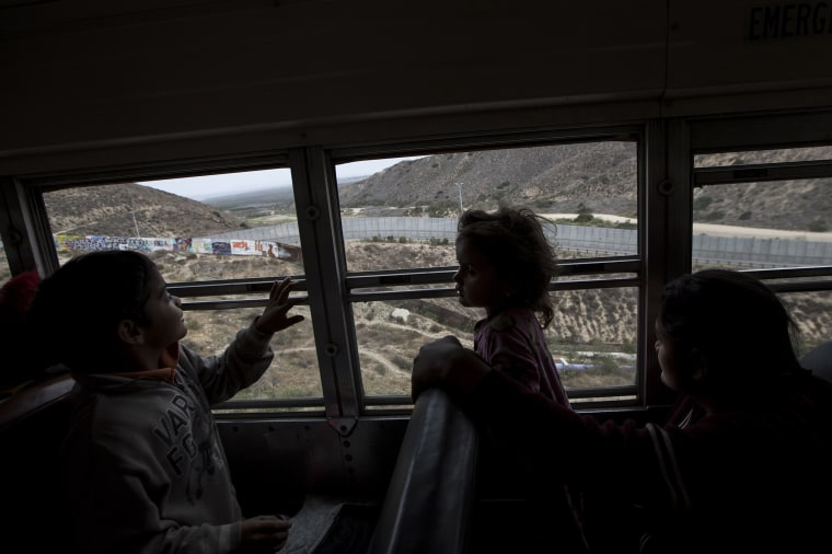 Image: Central American children who are traveling with a caravan of migrants look at the border wal