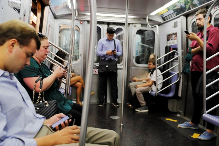 Image: Commuters using mobile phones