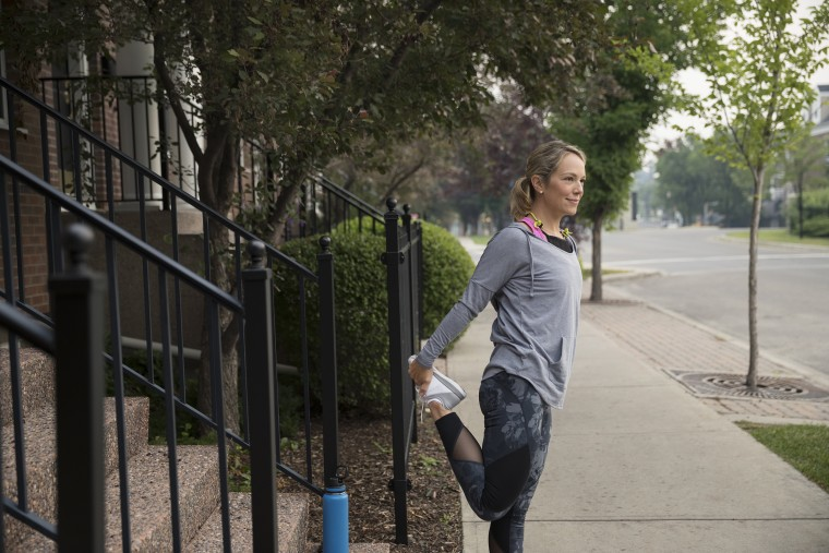 Image: Female runner stretching legs on sidewalk