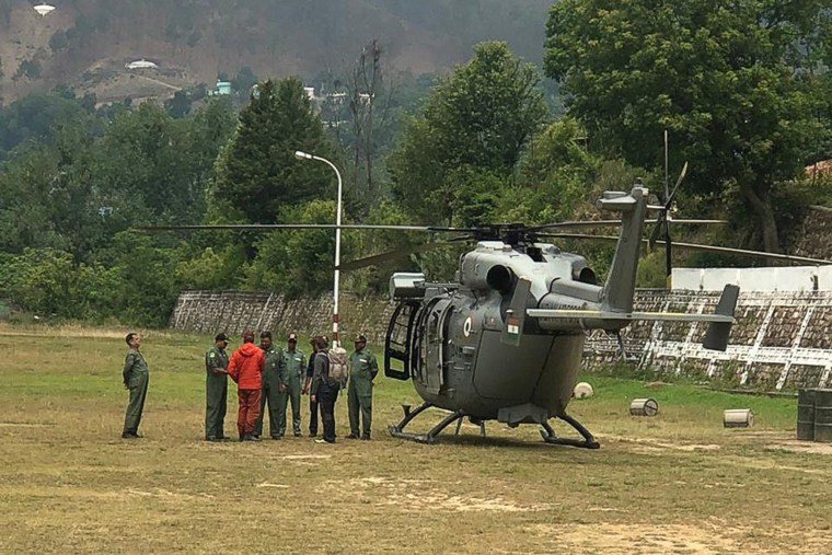 Image: Rescue mission team members stand next to an India Air Force (IAF) helicopter before take off from the Indo-Tibetan Border Police camp in Pithoragarh in the northern Indian state of Uttarakhand