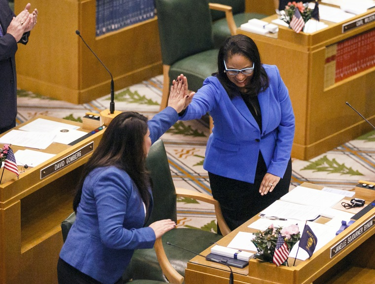 Rep. Teresa Alonso Leon, left, and Rep. Janelle Sojourner Bynum high-five after members of the House of Representatives are sworn into office at the Oregon State Capitol in Salem, Oregon on Jan. 9, 2017