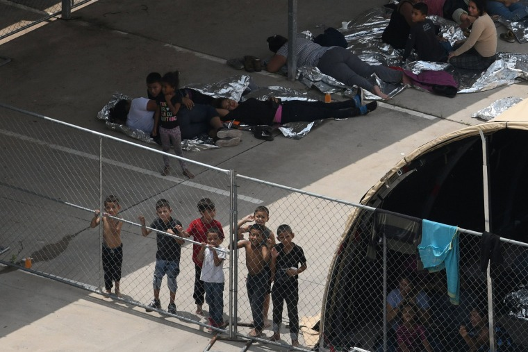 Image: Migrants are seen outside the U.S. Border Patrol McAllen Station in a makeshift encampment in McAllen