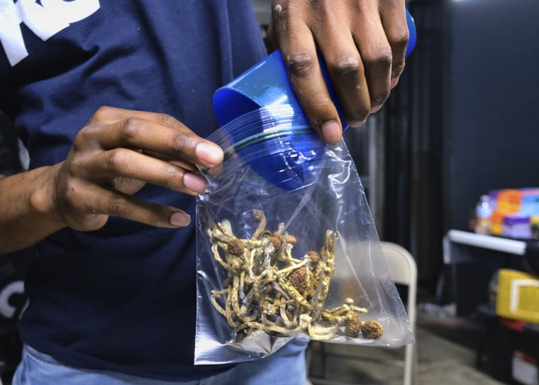 Image: A vendor bags psilocybin mushrooms at a cannabis marketplace in Los Angeles.