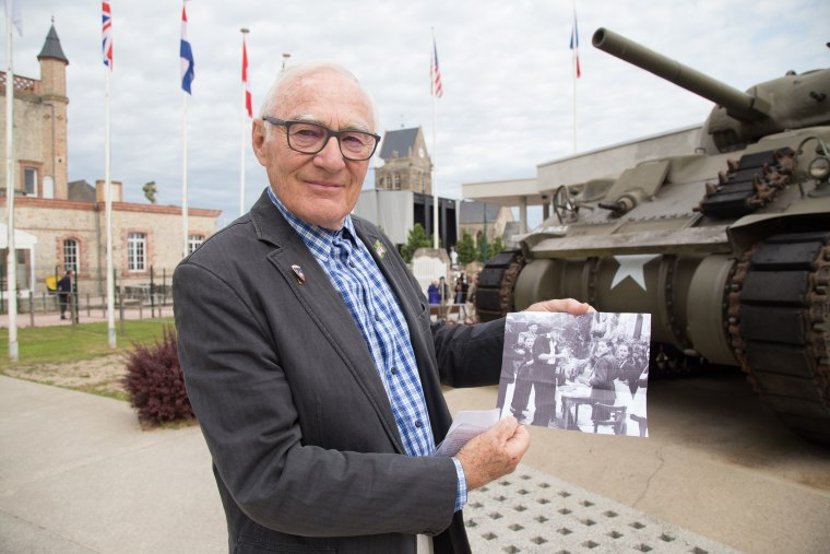 Image: Henry-Jean Renaud holds a photo of himself after the liberation outside of the Airborne Museum in Sainte-Mere-eglise