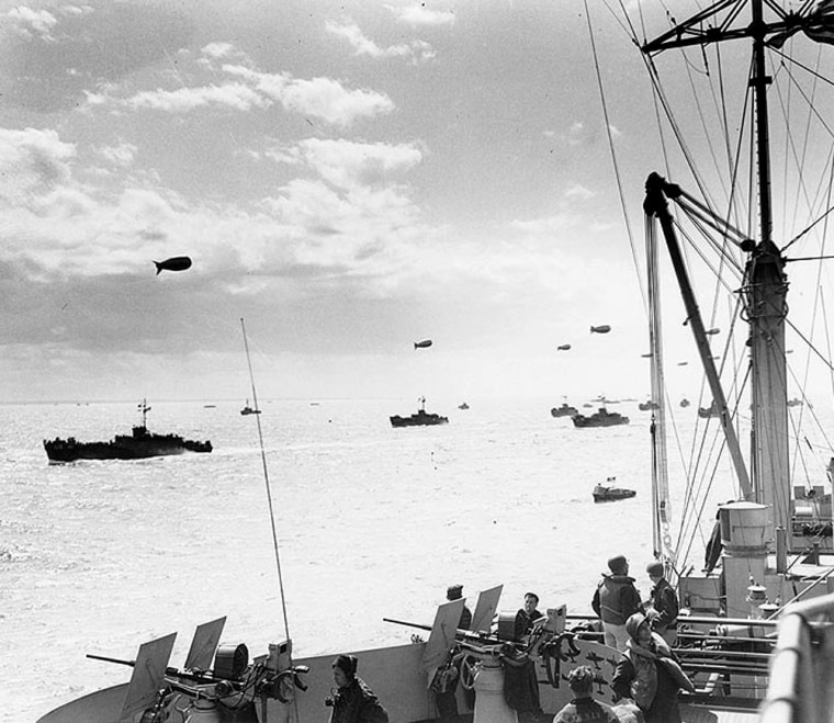 A convoy of infantry transport ships head toward the Normandy beaches on June 6, 1944, as seen from the USS Ancon. Barrage balloons, which defend against attack from loy-flying aircraft, float overhead.