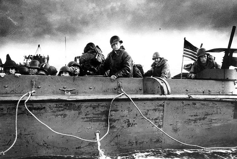 Troops on a landing craft approach a Normandy beach.