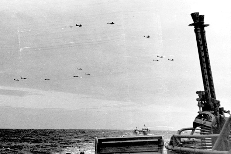 U.S. Navy PT boats cross the English Channel as B-1s, known as Flying Fortresses, fly overhead.