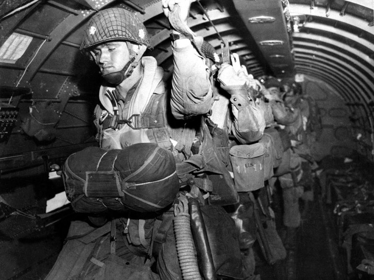 U.S. paratroopers fix their static lines ahead of a pre-dawn jump over Normandy on D-Day.