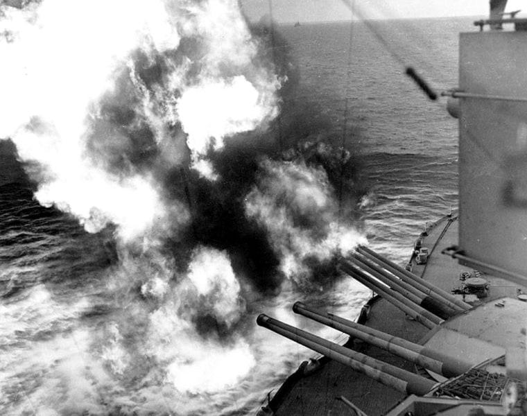 Forward guns of the USS Nevada (BB-36) fire on shoreline positions during the landings on Utah Beach.