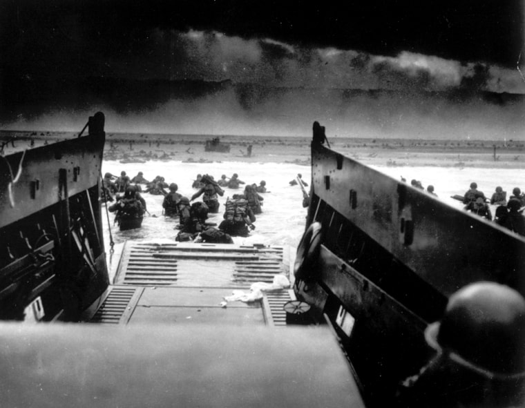 While under attack from heavy machine gun fire from the German coastal defense forces, American soldiers wade ashore off the ramp of a U.S. Coast Guard landing craft.