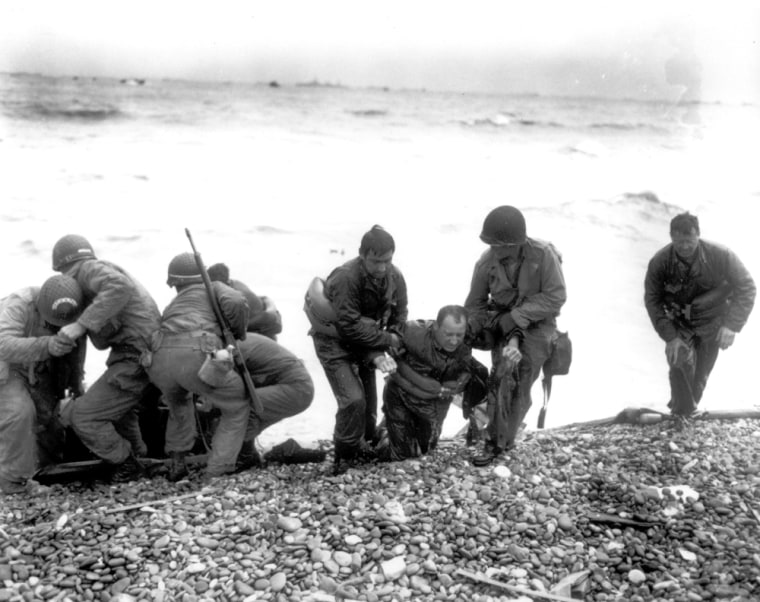 Members of an American landing unit help their exhausted comrades ashore. The men reached the zone code-named Utah Beach, near Sainte-Mere-Eglise, on a life raft, after their landing craft was hit and sunk by German coastal defenses.