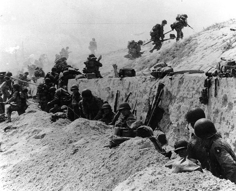 U.S. soldiers of the 8th Infantry Regiment, 4th Infantry Division, move over the Utah Beach seawall during the invasion.