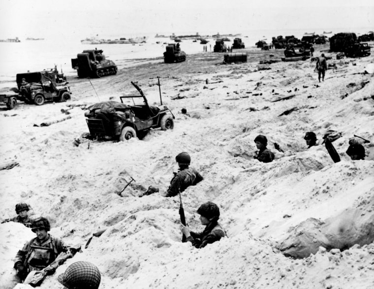 Sitting in the cover of their foxholes, American soldiers of the Allied Expeditionary Force secure a beachhead during the initial Normandy landing operations. In the background, amphibious tanks and other equipment crowd the beach, while landing craft bring more troops and material ashore.