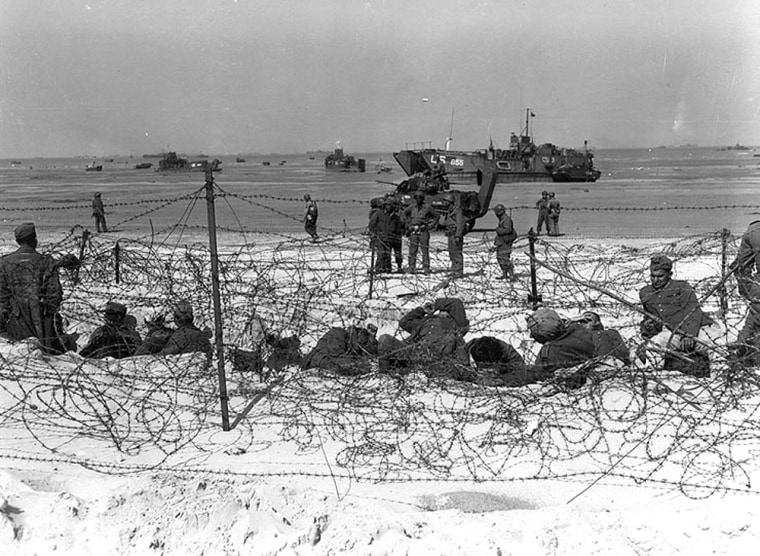 Prisoners of war sit inside a specially constructed enclosure on Utah Beach.