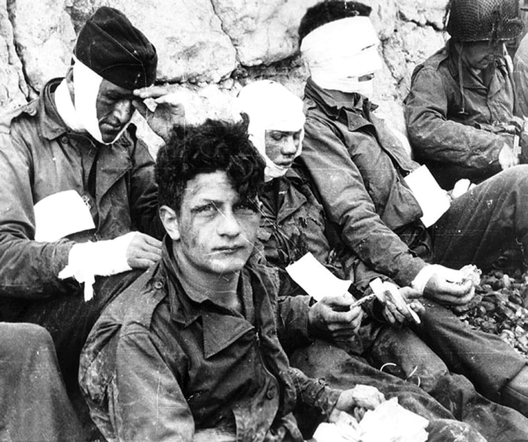 Army wounded are given cigarettes and food on Omaha Beach. The U.S. 1st Infantry Division suffered 2,500 casualties on the first day of the invasion.