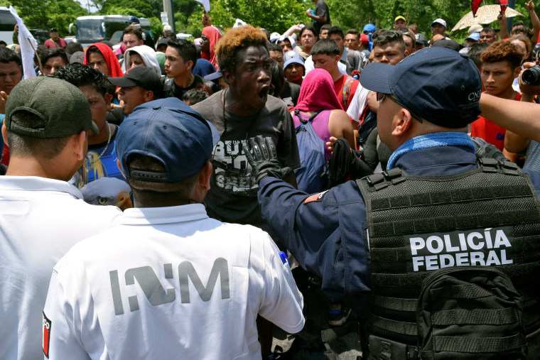 Image: A migrant argues with a federal police officer during a joint operation by the Mexican government to stop a caravan of Central American migrants on their way to the U.S., at Metapa de Dominguez