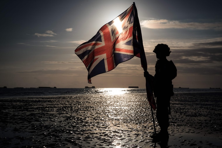 Image: A soldier holds an English flag on the beach of Arromanches