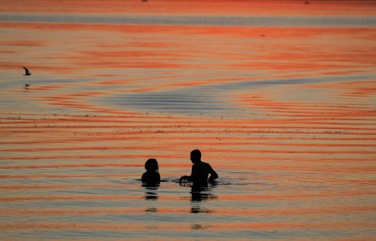 Image: People enjoy sunset in a lake on the outskirts of Minsk
