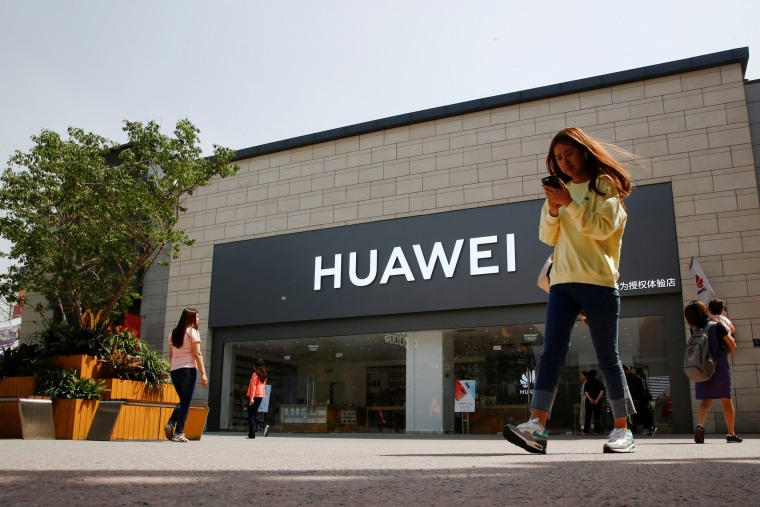 Image: FILE PHOTO: A woman looks at her phone as she walks past a Huawei shop in Beijing