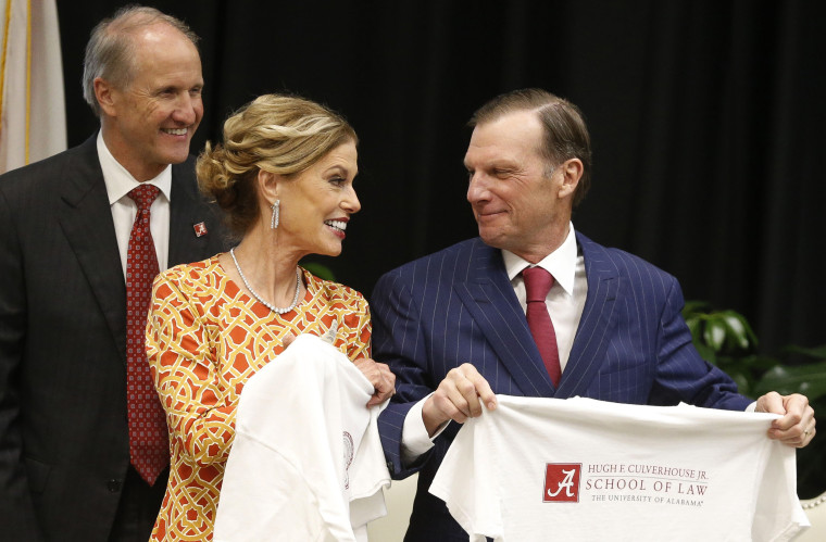 Image: Hugh F. Culverhouse Jr., right, and wife, Eliza show off t-shirts from the the University of Alabama law school, which bears his name, in Tuscaloosa, Alabama on Sept. 20, 2018.