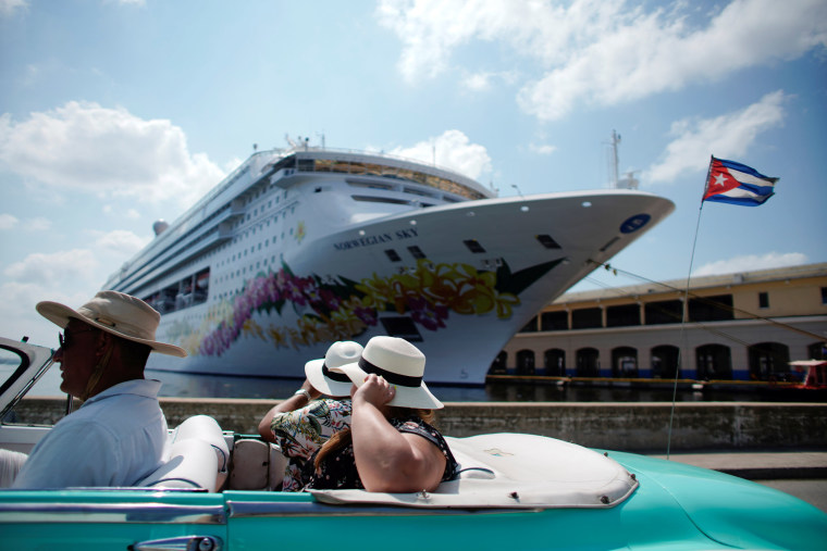 Image: Tourists ride inside a vintage car as they pass by the Norwegian Sky cruise ship in Havana
