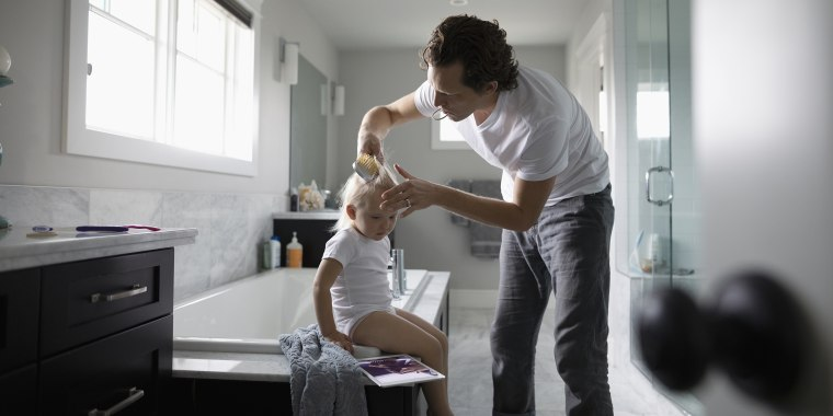 Father brushing toddler daughter's hair in bathroom