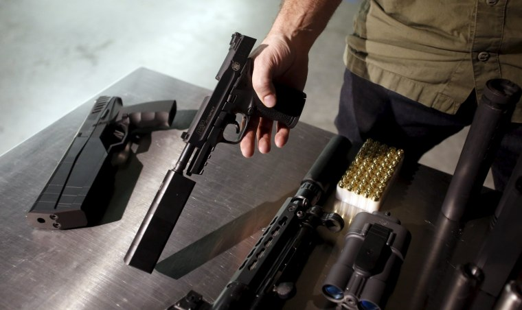Image: SilencerCo CEO Joshua Waldron shows guns with suppressors in West Valley City