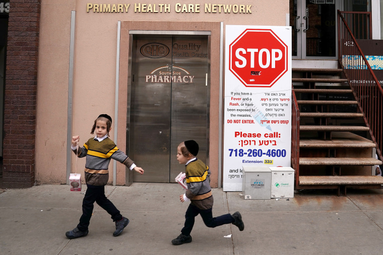 Image: Children walk past a sign advising about a measles outbreak in the Brooklyn Borough of New York