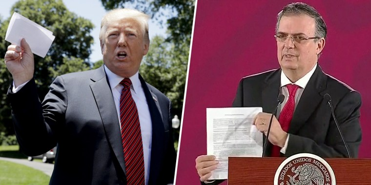 President Donald Trump waves a sheet of paper he claims contains a secret agreement with Mexico on Tuesday. On Monday, Mexican Foreign Secretary Marcelo Ebrard pointed to his own sheet of paper, saying no such secret agreement exists.