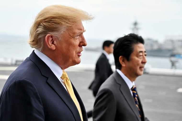 Image: President Donald Trump and Japanese Prime Minister Shinzo Abe walk aboard a helicopter carrier in Yokosuka on May 28, 2019.