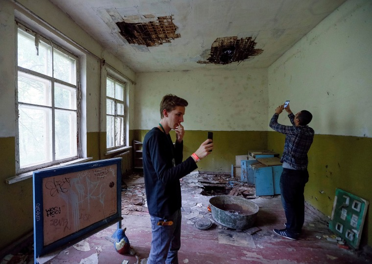 Image: Visitors take pictures at a kindergarten in the abandoned village of Kopachi, near the Chernobyl Nuclear Power Plant