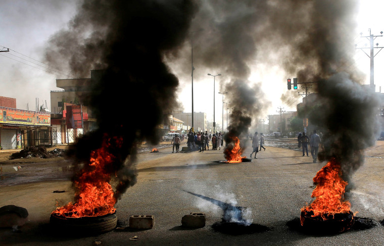 Image: Sudanese protesters use burning tyres to erect a barricade on a street, demanding that the country's Transitional Military Council hand over power to civilians, in Khartoum