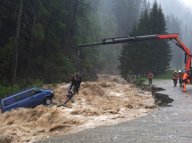 Image: Two occupants of stranded van are lifted unhurt by a crane during heavy rain in Spluegen
