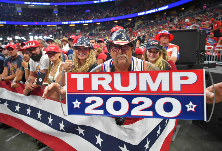 Image: A man holds up a sign as the crowd waits for President Donald Trump to arrive at a rally at the Amway Center in Orlando, Florida to officially launch his 2020 campaign